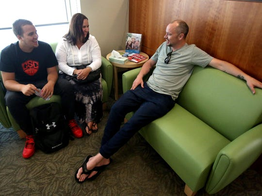 Kyle Atkinson talks with his mother, Holley Oglesby, and friend and former coach Mike McShane before radiation therapy treatment at Oregon Health and Science University on Thursday, July 2, 2015, in Portland, Ore.