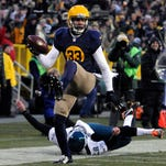 Green Bay Packers' Micah Hyde (33) gets by Philadelphia Eagles punter Donnie Jones (8) for a 75-yard touchdown in the first quarter at Lambeau Field.