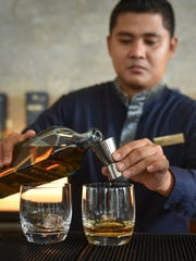 Bartender Christian Bautista uses a two-ounce jigger to pour whiskey at the limited edition Guam Johnnie Walker Blue bottle unveiling at the Dusit Thani Guam Resort on July 30.