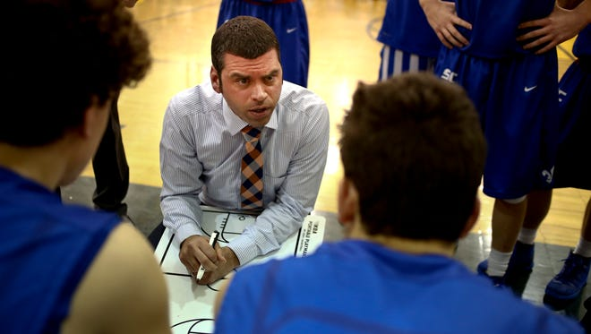 St. Clair coach Shawn Sharrow talks with players. during a high school basketball game.