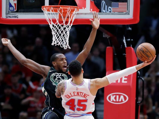 Milwaukee Bucks forward Khris Middleton, left, guards against Chicago Bulls guard Denzel Valentine during the first half of an NBA basketball game Friday, March 23, 2018, in Chicago. (AP Photo/Nam Y. Huh)