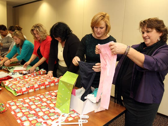 Volunteers, who are all employees of VNA Health Group, wrap gifts Wednesday for the Seasons of Hope project. The seasonal project provides gifts for 700 needy families in the VNA service area, which includes Middlesex County; the volunteers are working in the office building located in Red Bank,. Far right, Bridget Murphy of Wall, chief philanthropy officer, and Pauline De Palma, of Spring Lake Heights, manager of volunteer services, pack a box of clothing.