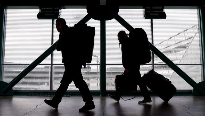 Travelers walk on Dec. 21, 2012, to a ticketing desk at O'Hare International Airport in Chicago.