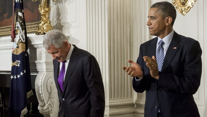Secretary of Defense Chuck Hagel bows his head as President Obama applauds after announcing his resignation at the White House in Washington, DC, November 24, 2014. Hagel will remain at his post until a successor is neamed and confirmed by the Senate.