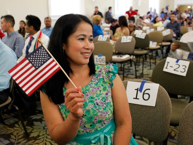 Juliet Lichtefeld, from the Philippines, has her photo taken by a friend before the naturalization ceremony at the main branch of the Louisville Free Public Library. There were 148 candidates, representing 48 countries from around the world, sworn in as new United States Citizens by the U.S. District Court for the Western District of Kentucky.  June 27, 2014