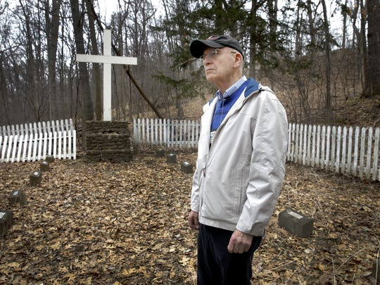 The Rev. Charles Grimm, the Industry Residential Center's retired chaplain, walks through the abandoned cemetery in Rush.