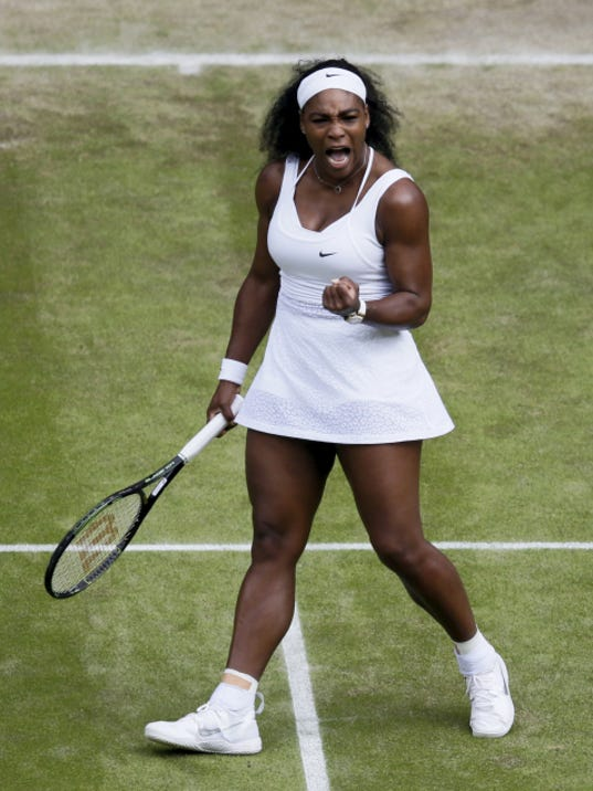 Serena Williams celebrates winning a point against Victoria Azarenka during their singles match at the All England Lawn Tennis Championships in Wimbledon, London, on Tuesday. Williams rallied for a three-set win.