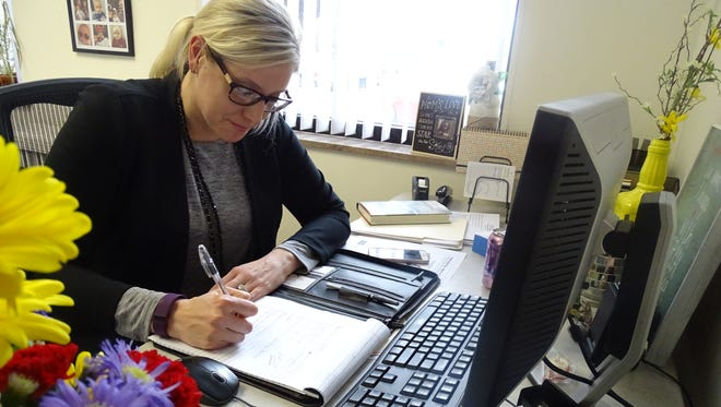 Erin Stine takes notes in her new office at Crawford 20/20 Vision after taking over Monday as the organization's community development director.
