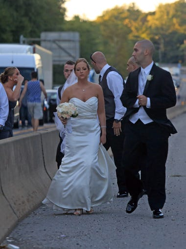 Newlyweds Robert and Katherine  Mitariten walk down the median on I-287 after being stuck in traffic for over an hour in route to their wedding reception at Fountainhead on Sept. 12, 2014.