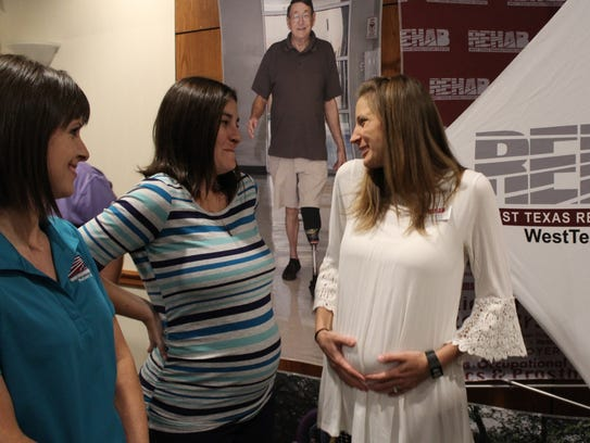 Sara Snowden, right, holds her tummy while talking