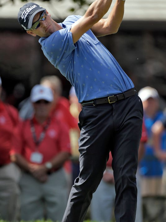 Adam Scott, of Asutralia, hits his tee shot on the first hole during a