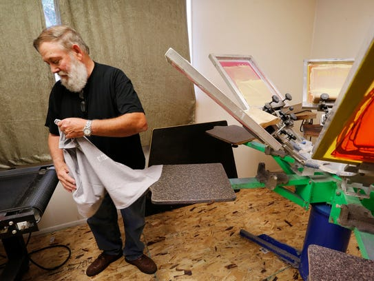 Owner Dick Mullen removes a custom T-shirt from a six
