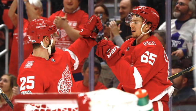 Red Wings defenseman Danny DeKeyser (65) is congratulated by defenseman Mike Green after scoring a goal in the second period of the Wings' 3-1 win on Friday at Little Caesars Arena.