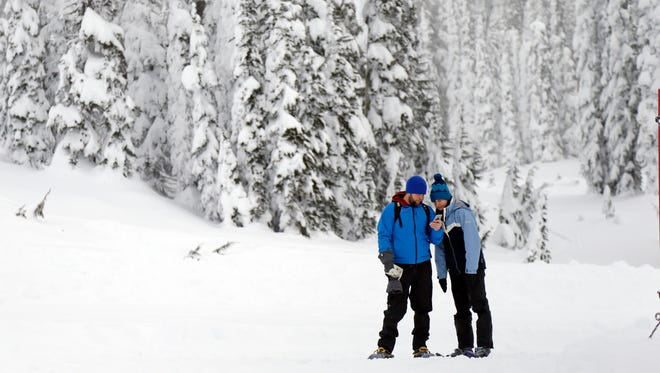 In this photo taken Friday, Dec. 16, 2016, snowshoers look at a cellphone while in the backcountry near the Paradise area at Mount Rainier National Park, Wash. Spotty or no cellular service has been the norm at the nation's fifth oldest park south of Seattle, but that could change soon. Mount Rainier National Park is considering proposals to provide cellular service in the park, setting off debates about whether people enjoying the park and surrounding wilderness areas should have access to calls and social media while in nature. (AP Photo/Elaine Thompson)