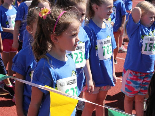 Lillian Duchateau, 6, listens to the volunteers before the start of the kindergarten girls run at Awesome 3000 on Saturday, May 7, 2016.