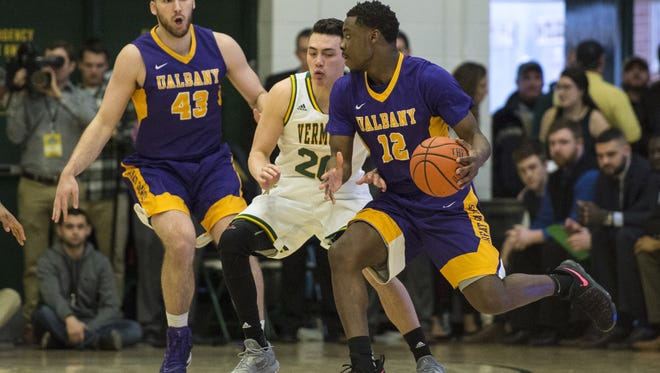 University of Albany forward  Devonte Campbell (12) dribbles the ball against the Vermont Catamounts' Ernie Duncan of Evansville during the first half of Saturday's Amerca East Championship game. Vermont won 56-53.
