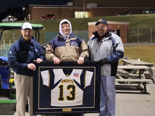The jersey represents the first year for varsity boys' and girls' lacrosse in 2013.  Standing from left to right are:  Dr. Tim Mitzel, EYHS Principal, Jack Predix, EYHS Athletic Director and Mark Keller, President of the school board.