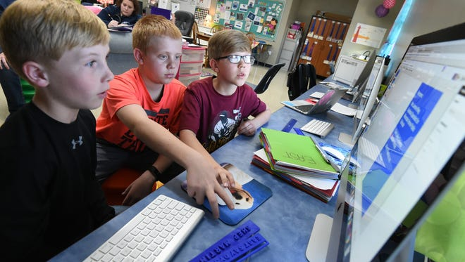 Blaine Tate (left), 10, Brady Lance (middle), 11, and Braxton Carson, 10, finalize their presentation for the National Service Competition, which is set for March 15 in Hot Springs. The trio improved line readers by 3-D printing them to help dyslexic students.