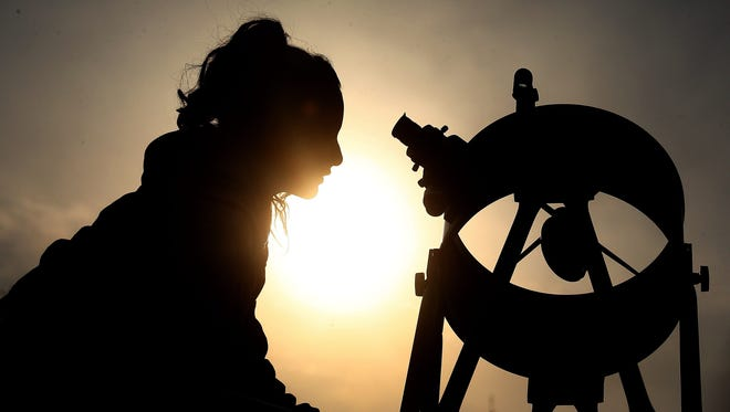 A woman looks through a solar telescope during an astronomical observation at the Chilean Skies Observatory, in Santiago de Chile, Chile, on Oct. 22 2016. Thirty people participated in a daytime astronomical observation with a dozen telescopes that allowed them to see the sun, planets such as Venus, Mars and Saturn and some stars.