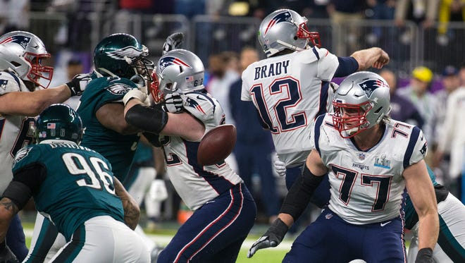 Brandon Graham, second from left, forces Patriots quarterback Tom Brady to fumble the ball in the Eagles' 41-33 win in the Super Bowl on Feb. 4. Graham revealed Thursday that he played that game with a high ankle sprain.