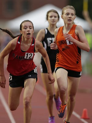 Iola-Scandinavia's Erika Kisting and Flambeau's Rachel Lawton cross the finish line in the Div. 3 3,200-meter run during the WIAA state track and field meet at Veterans Memorial Field Sports Complex in La Crosse Friday.