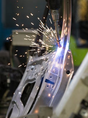 A robotic arm welds a door for a Honda Civic on the day of an announcement of 100 new jobs coming to the Honda Manufacturing of Indiana facility in Greensburg, which will work on the CR-V compact SUV.