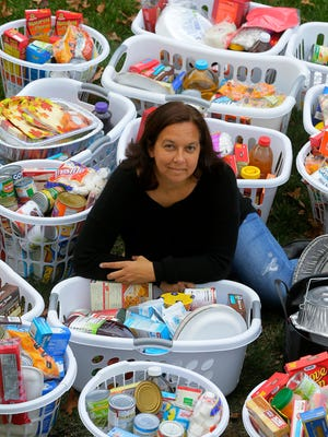 Jamie Bruno of Manalapan, who assembles and distributes baskets of food for Thanksgiving dinners to the area's needy, poses with some of the baskets at her home  in Manalapan, NJ Wednesday, November 16, 2016.