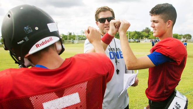 Ida Baker High School football coach Brian Conn encourages quarterbacks David Drennan, left, and Toby Noland, right, during practice Wednesday (9/28/16) at Gulf Middle School in Cape Coral. Ida Baker takes on Cape Coral on Friday.