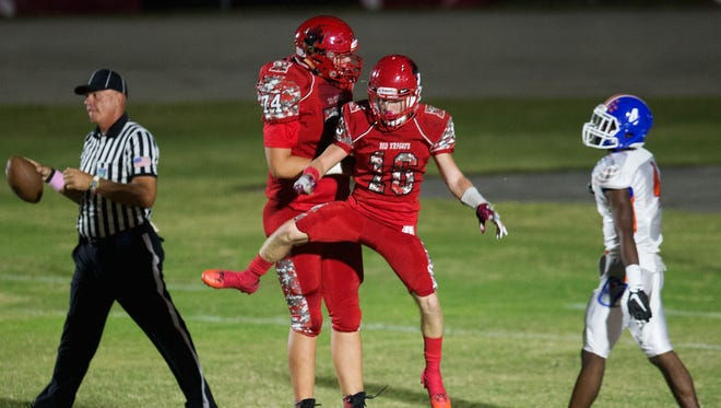 North Fort Myers High School's Blaise Sparks (74) and Clayton Savinsky (10) celebrate a touchdown scored by Savinsky against Cape Coral during second quarter play Friday (10/27/17) at North Fort Myers High School.