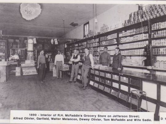 The interior of R.H. McFaddin's Grocery Store on Jefferson Street in 1890. Pictured are Alfred Olivier, a Mr. Garfield, Walter Melancon, Dewey Olivier, Tom McFaddin and wife Sadie.
