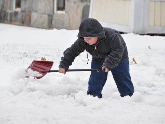 With his dad Tom close by, Justin Wesolowski, 7, uses his tiny shovel to pick up snow in front of their home in Adams, Mass., on Sunday.