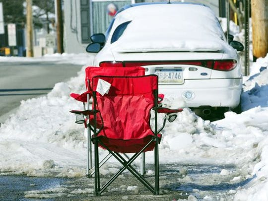 "Folding chairs used as ""dibs"" for a parking space shoveled out parking space."