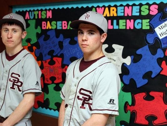 South River High School baseball players Chris Talbot (left) and Nick Lepore (right) pose for a photograph last year on in front of the school's bulletin board which promotes the Autism Awareness Baseball Challenge.