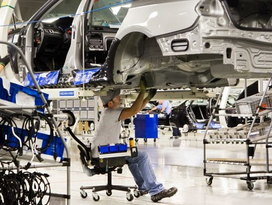 An employee works on a Passat sedan at the Volkswagen