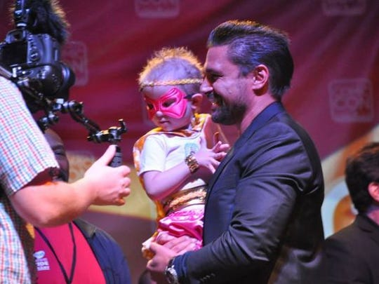 "Actor Manu Bennett, known for his role as Azog in ""The Hobbit"" films, holds a child who is part of the Make A Wish Foundation at Salt Lake Comic Con on Sept. 4, 2014, in Salt Lake City."