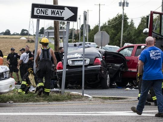 Authorities investigate the scene after a fatal crash between a limousine and a pickup truck Saturday, July 18, 2015, in Cutchogue, N.Y.