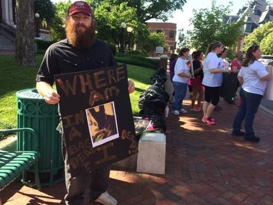 Jonathon Pigott of Clarksville protests with about 40 others outside the Montgomery County Courthouse on Friday. He said he was supposed to send his dog to Nicole Hulbig for training but she was arrested on aggravated animal cruelty first.