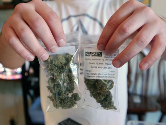 Chris Hewitt holds up 7 gram bags of marijuana buds