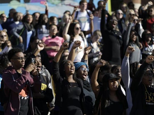 Students cheer while listening to members of a black