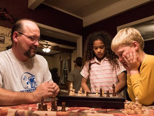 Scott Ness plays a game of chess with Brad, 9, while