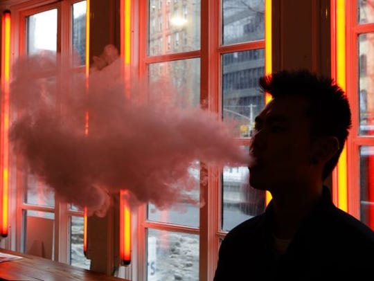 A  man exhales vapor from an e-cigarette in New York.