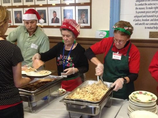 Volunteers serve food during the Bandera Family Christmas