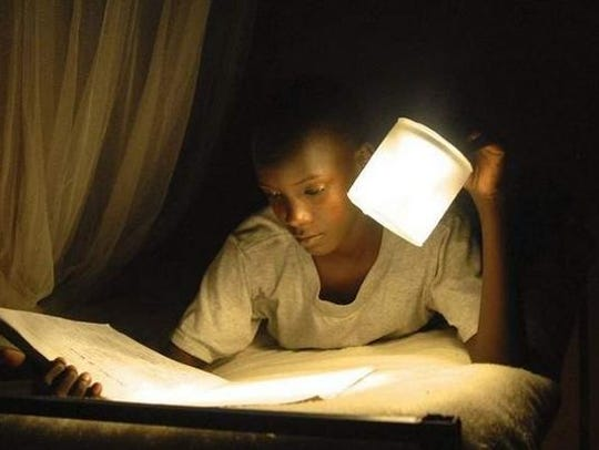 A Ugandan student uses a Luci light.