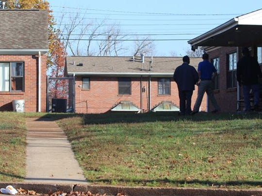 Clarksville Housing Authority workers in November 2015 examine a porch where a car tore down three beams as it passed between the buildings on the right and left and then went down an embankment after a fatal shooting.