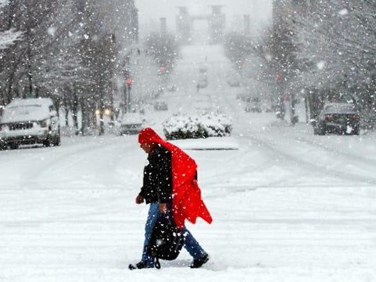 A man walks through heavy snow in downtown Nashville, Tenn., on Jan. 22, 2016.