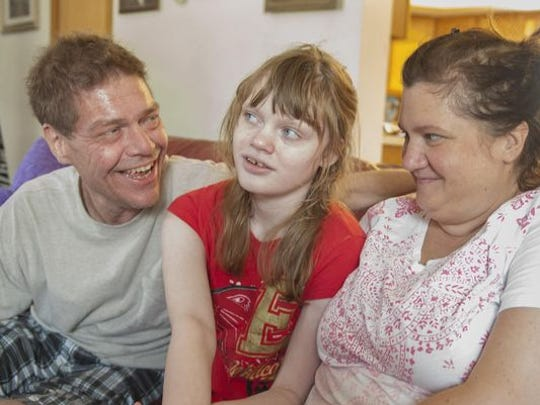 Medical marijuana patient Genny Barbour, center, who is autistic and suffers from seizures, with her parents Roger and Lora, at their home in Maple Shade, N.J. The 16-year-old fought to be able to use her medicine at school.