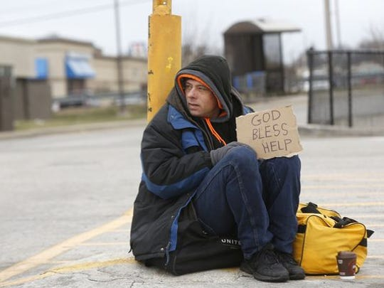 A Springfield panhandler sat between the Walmart and McDonald's restaurant on N. Kansas Expressway in December 2015.