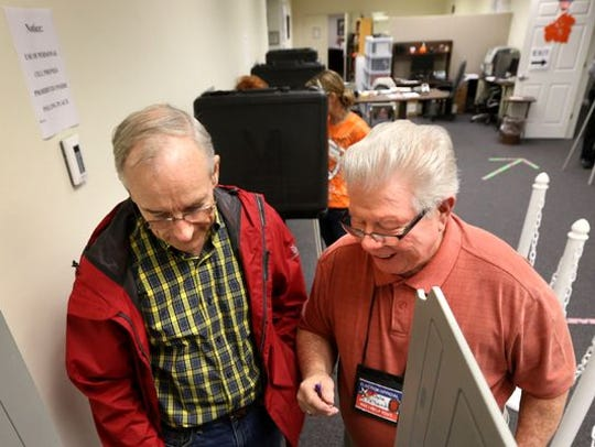 Poll worker Dale Polland, right, goes over voting procedures