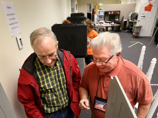 Poll worker Dale Polland, right, goes over voting procedures with Paul Sanders on on a previous early voting day at the Rutherford County Election Commission office on the south side of the Square in Murfreesboro.