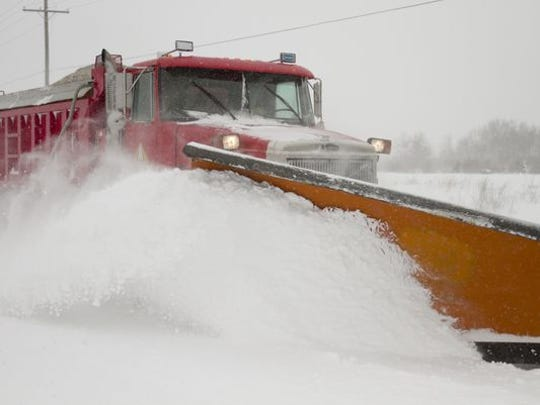 Brad Smith of the Livingston County Road Commission plows Runyan Lake Road south of Clyde Road in Hartland Township. Several schools have been close Monday due to the snow storm.